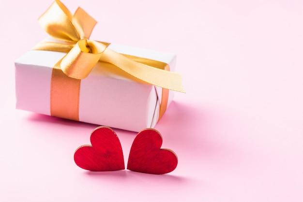 Confezione regalo bianca di san valentino con un fiocco dorato e un biglietto di auguri di composizione in cuori rossi di legno