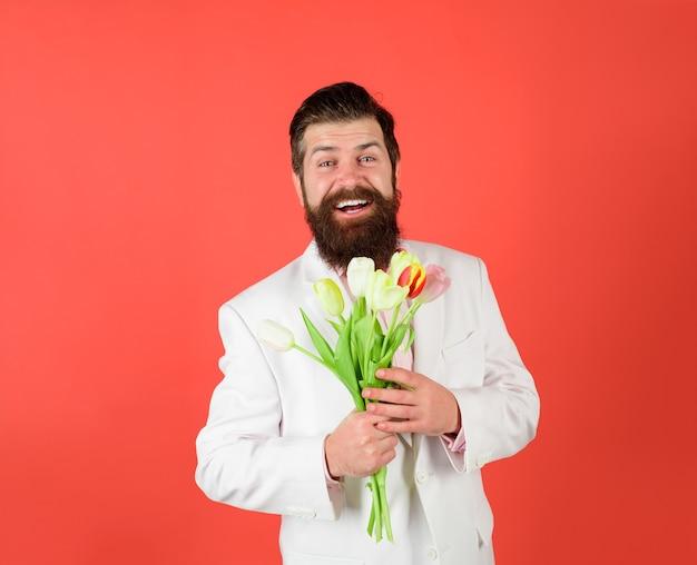 Il giorno di san valentino, il compleanno delle donne, l'uomo bello fiorisce l'uomo d'affari con un mazzo di tulipani per