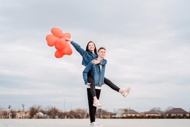 San valentino. giovani coppie amorose che abbracciano e che tengono i palloncini a forma di cuore rosso all'aperto