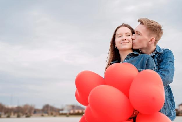 San valentino. giovani coppie amorose che abbracciano e si baciano tenendo palloncini a forma di cuore rosso all'aperto