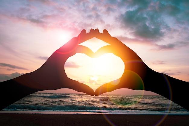 Il concetto di giorno di san valentino, la mano della siluetta fa la forma del cuore con il cielo e la luce del sole di vista sul mare.