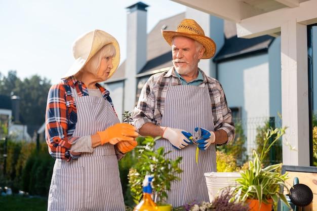 Momenti preziosi. coppia intenzionale laboriosa che si prende cura di piante e fiori mentre si lavora in giardino
