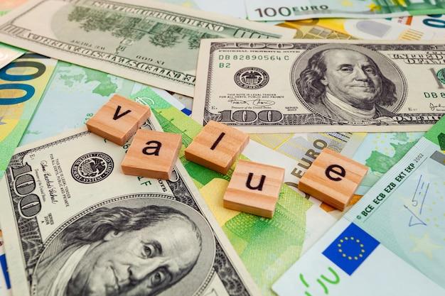 Iscrizione value su cubi di legno sulla trama di dollari americani e banconote in euro