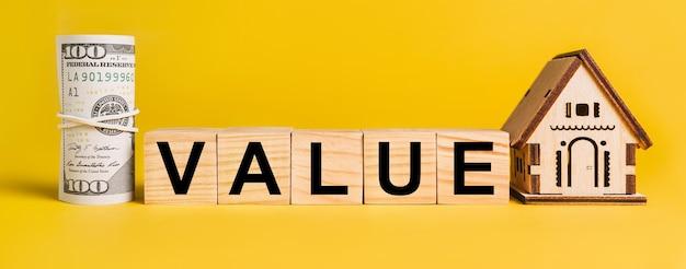 Value con modello di casa in miniatura e denaro su sfondo giallo. il concetto di affari, finanza, credito, tasse, immobili, casa, alloggio