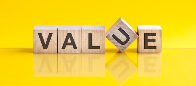 La parola di valore è fatta di blocchi di legno che giacciono sul tavolo giallo, concetto