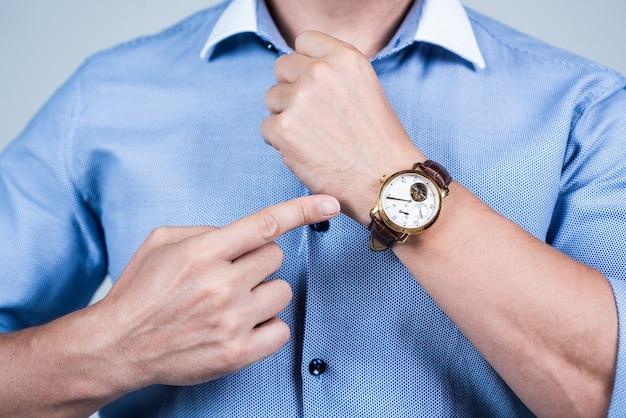 Valuta il tuo tempo il manager ha ritagliato il punto di vista dito sull'orologio da polso riunione sulla gestione del tempo