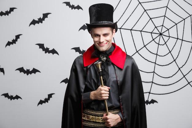 Concetto di halloween del vampiro - ritratto del vampiro caucasico bello in costume nero e rosso di halloween che canta con il personale.
