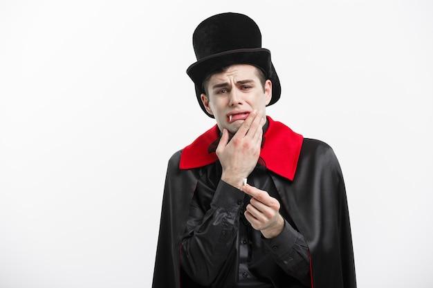 Concetto di halloween del vampiro - ritratto del vampiro caucasico bello che fa male perde il suo dente del vampiro.