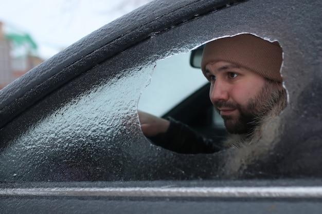 Vandalismo inverno uomo ha rotto il vetro dell'auto un sassolino