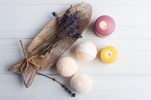 Bombe da bagno aromatiche alla vaniglia nella composizione spa con fiori di lavanda secca e asciugamani, distesi