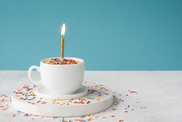 Torta di compleanno alla vaniglia con granelli di zucchero di colore e candela accesa