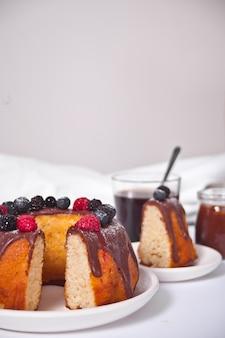Torta alla vaniglia con frutti di bosco e un bicchiere di caffè sullo sfondo.