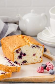 Torta alla vaniglia o pan di spagna con mirtilli su una tavola su uno sfondo grigio cemento. copia spazio.