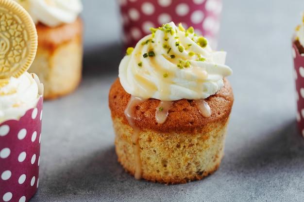 Cupcakes alla vaniglia con crema e caramello su sfondo grigio da tavola.