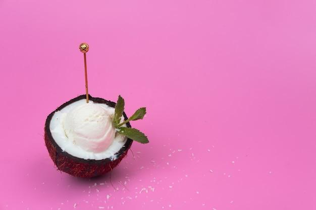 Pallina di gelato alla vaniglia in cocco fresco per metà decorata con foglie di menta su fondo rosa