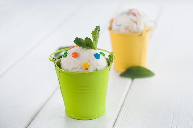 Pallina di gelato alla vaniglia in piccoli secchi