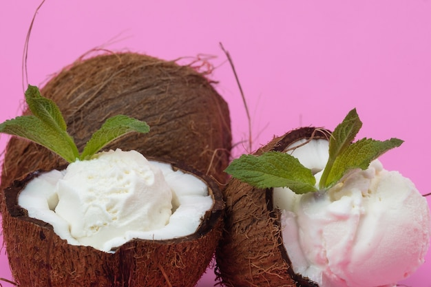 Palline di gelato alla vaniglia in metà di cocco fresco decorate con foglie di menta su sfondo rosa.
