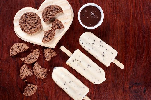Gelato alla vaniglia ricoperto di cioccolato bianco e farcito con crema alla nocciola. ghiacciolo. vista dall'alto