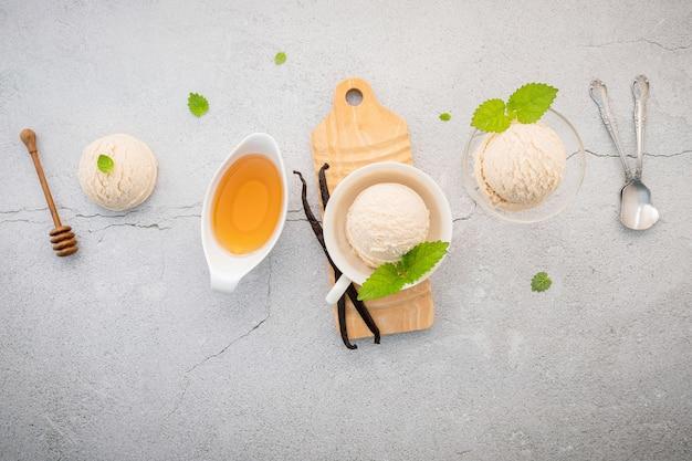 Sapore di gelato alla vaniglia in ciotola con baccelli di vaniglia installati su cemento.