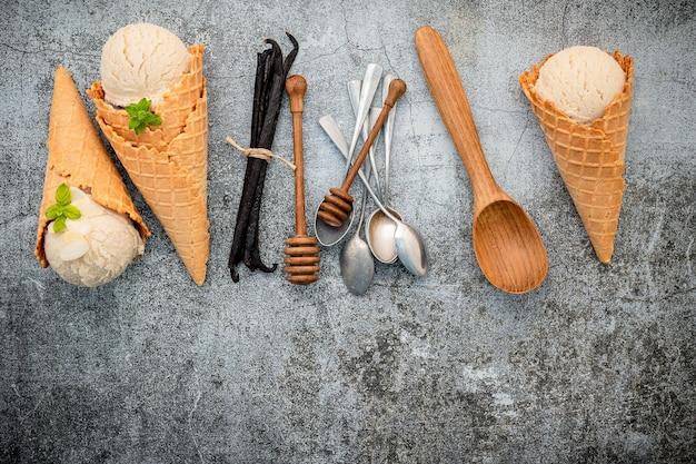 Sapore di gelato alla vaniglia in coni con baccelli di vaniglia installati su fondo in cemento
