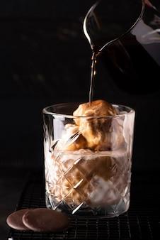 Gelato alla vaniglia con caffè freddo in un bicchiere su uno sfondo nero
