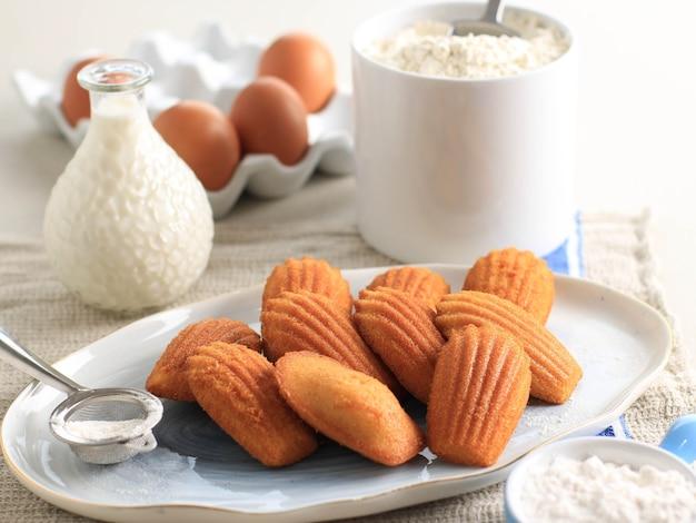 Madeleine alla vaniglia su piatto in ceramica ovale bianco. famosa torta di pasta frolla dolce francese, solitamente servita con spolverata di zucchero