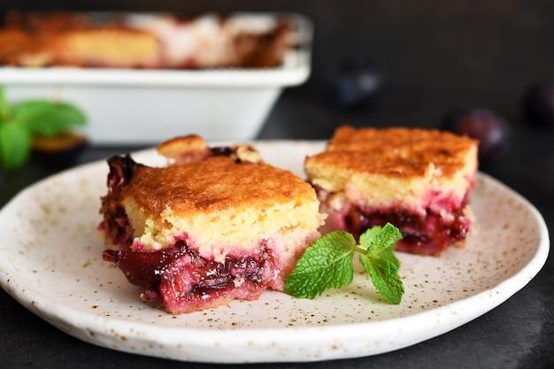 Muffin alla vaniglia con prugne e menta su fondo di cemento scuro. torta di frutta.