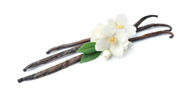 Bastoncini di vaniglia con fiori su bianco