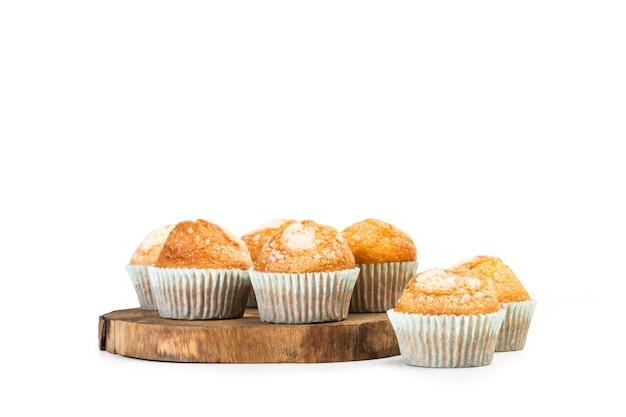 Cupcakes alla vaniglia e zucchero su un anello di tronco d'albero su uno sfondo bianco