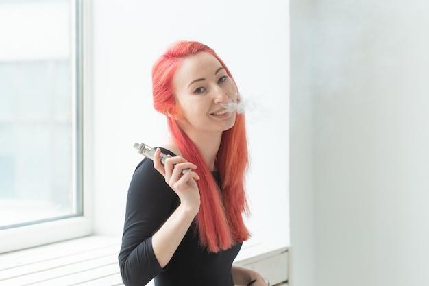 Vape, dipendenza e concetto di persone - la donna con i capelli rossi sta fumando vape.