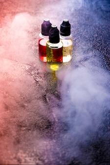 Bottiglie del liquido delle nuvole di fumo di concetto di vape