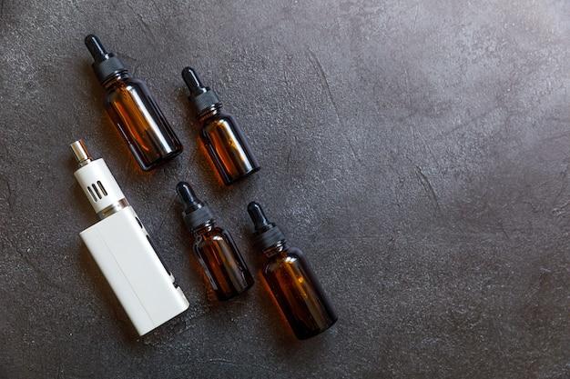 Dispositivo di svapo sigaretta elettronica sigaretta elettronica e bottiglie di liquidi su sfondo di pietra nera di scisto