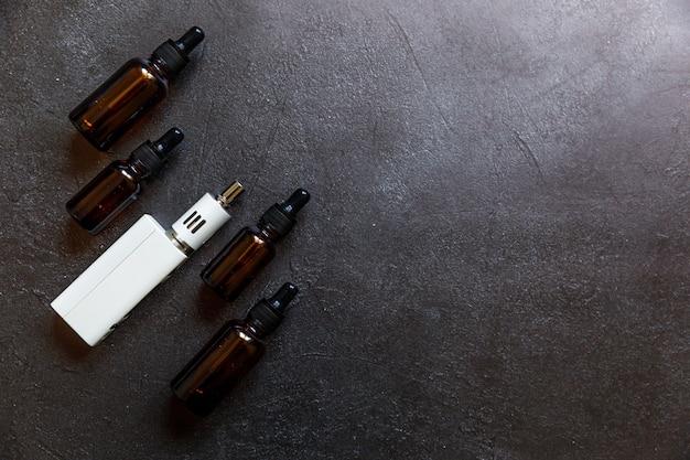 Dispositivo di svapo sigaretta elettronica sigaretta elettronica e bottiglie di liquidi su pietra nera