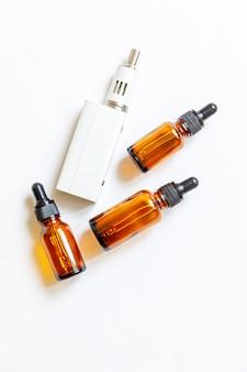 Vaping dispositivo e-sigaretta sigaretta elettronica e bottiglie di liquidi isolati su sfondo bianco. dispositivo di svapo per il fumo alternativo. concetto di negozio di svapo. gadget per vaper. accessori per lo svapo.