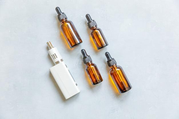 Dispositivo di svapo sigaretta elettronica sigaretta elettronica e bottiglie di liquidi su sfondo grigio pietra