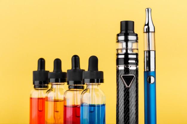 Dispositivi di svapo e bottiglie con liquido vap su sfondo giallo