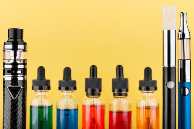 Dispositivi di svapo e bottiglie con liquido vap su sfondo giallo Foto Premium