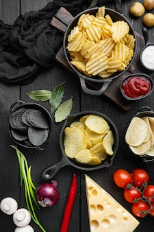 Variazione diverse patatine fritte con formaggio e cipolla, su fondo di legno nero, vista dall'alto piatta