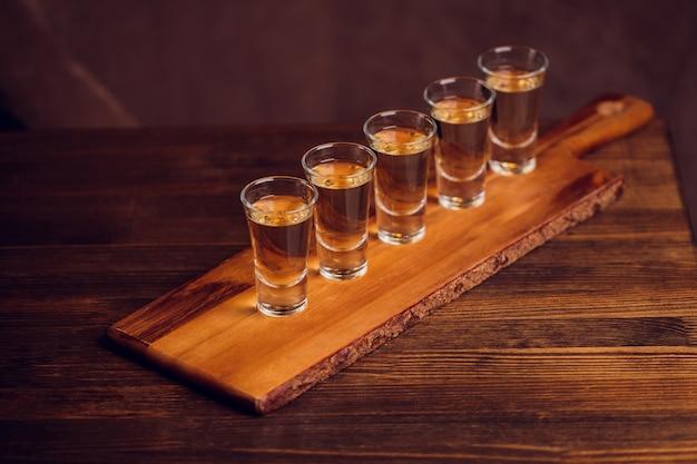 Variazione di hard shot alcolici serviti sul bancone del bar. blur bottiglie sullo sfondo.