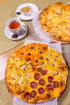 Pizze varie con salsa. su un tavolo di legno.