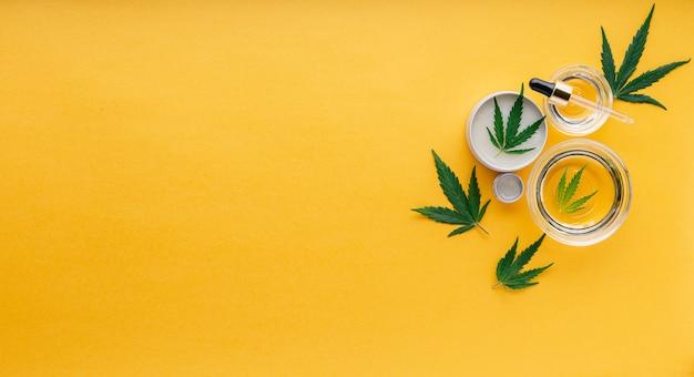 Varietà di oli di canapa cbd, burro. tintura di canapa con foglie. impostare prodotti cosmetici a base di cannabis o alimenti con cannabis medica con spazio di copia su sfondo giallo.
