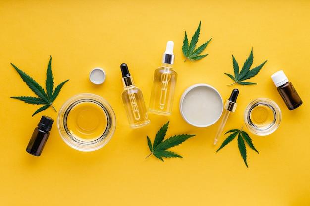 Varietà di oli di canapa cbd, olio essenziale, burro di siero. tintura di canapa. impostare prodotti cosmetici a base di cannabis con cannabis medica su sfondo giallo.