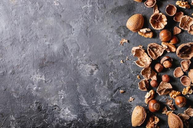 Varietà di frutta secca: mandorle, nocciole e noci su sfondo scuro. vista dall'alto, piatto. copia spazio