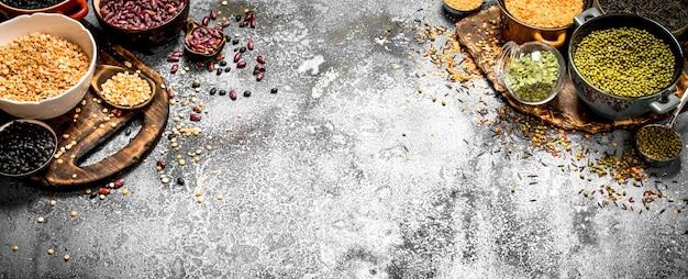 Varietà di semi di fagioli in una ciotola su fondo rustico.