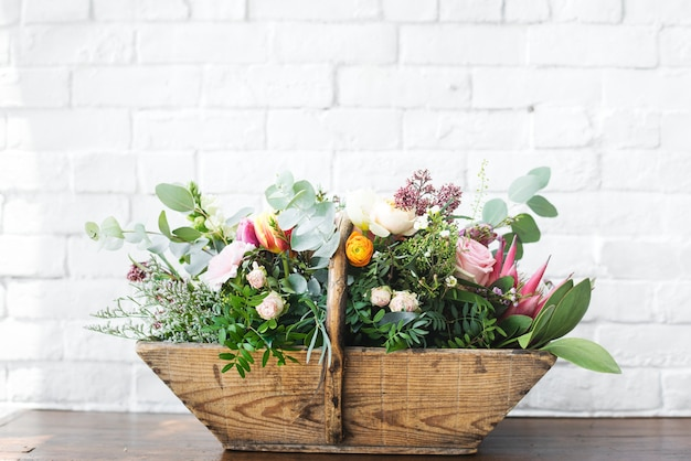 Varietà di bellissimi fiori in cestino di legno
