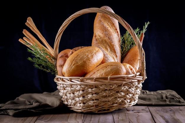 Varietà di pane nel cestino sulla tavola di legno nel buio