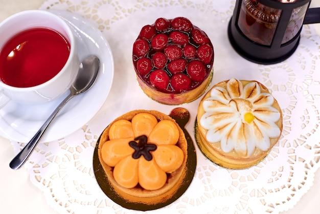 Varietà di torte con tè rosso su pizzo bianco.