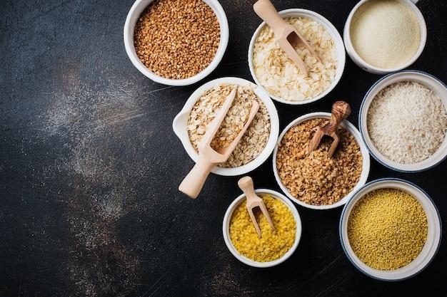 Varietà di fiocchi di cereali riso, miglio, grano saraceno, farina d'avena. superfood in ciotole di ceramica bianca su vecchio cemento scuro