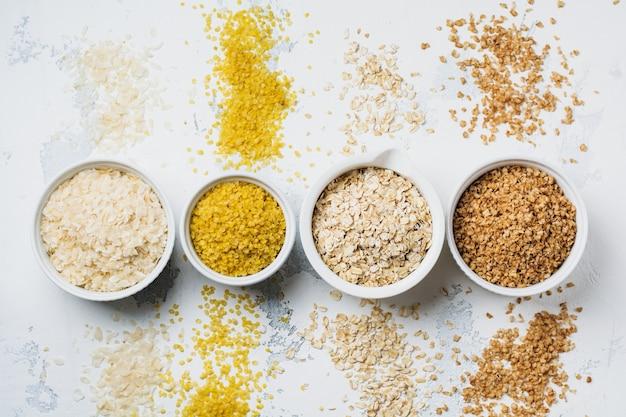 Varietà di fiocchi di cereali riso, miglio, grano saraceno, farina d'avena. superfood in ciotole di ceramica bianca di legno