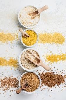 Varietà di fiocchi di cereali riso, miglio, grano saraceno, farina d'avena. superfood in ciotole di ceramica bianca